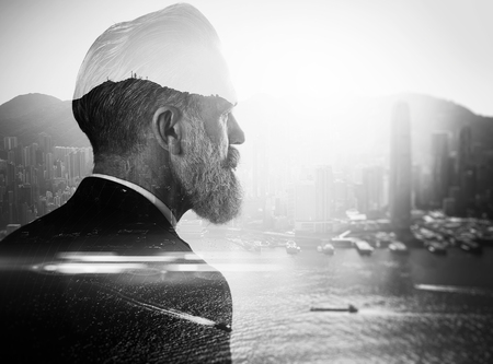 50792310 - stylish businessman in a suit looking at the horizon. photo of double exposure of the city. black and white